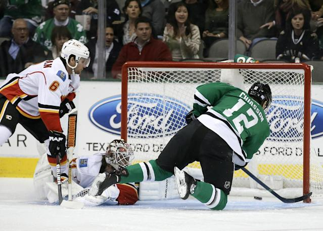 Calgary Flames defenseman Dennis Wideman (6) and goalie Karri Ramo, center, of Finland, watch as Dallas Stars' Alex Chiasson (12) scores from his knees in the first period of an NHL hockey game on Thursday, Oct. 24, 2013, in Dallas. (AP Photo/Tony Gutierrez)