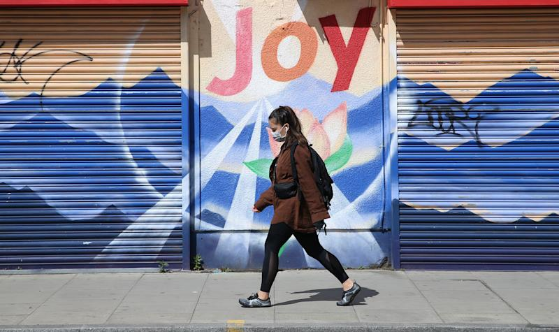"A woman wearing a face mask walks past a graffiti that reads ""Joy"" in Dalston, Hackney, east London, as the UK continues in lockdown to help curb the spread of the coronavirus. Picture date: Saturday May 2, 2020."