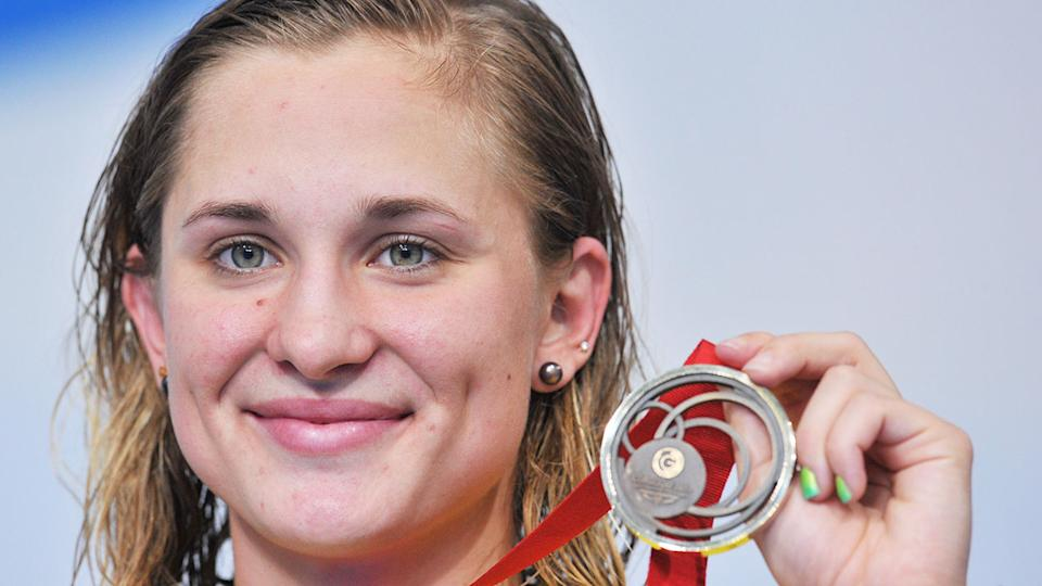 Pictured here, Maddie Groves holds one of her swimming medals aloft.