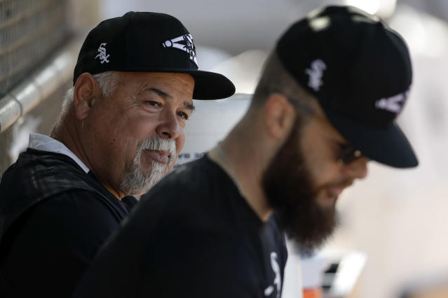 Chicago White Sox manager Rick Renteria, left, talks with pitcher Dallas Keuchel, right, during spring training baseball Saturday, Feb. 15, 2020, in Phoenix. (AP Photo/Gregory Bull)