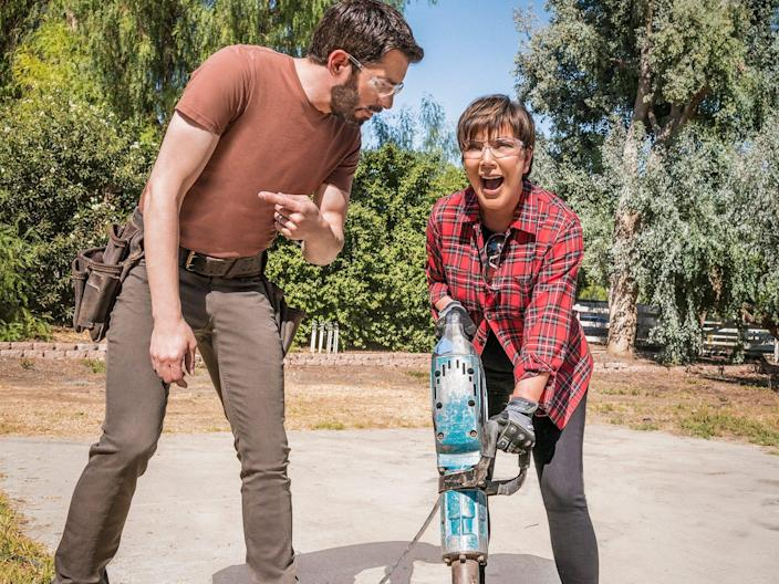 Kris Jenner uses a jackhammer while a Property Brother looks on.