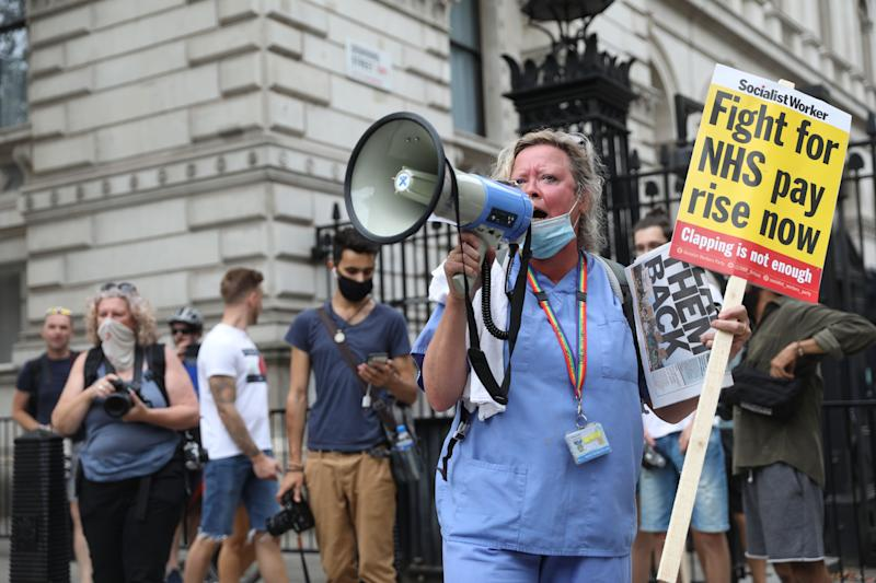 A NHS (National Health Service) worker protests outside Downing Street during a march through the streets of London on August 8, 2020, to demand a pay rise. (Photo by ISABEL INFANTES / AFP) (Photo by ISABEL INFANTES/AFP via Getty Images)