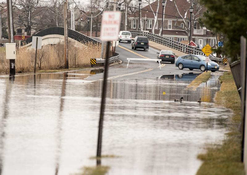 Cars are turned around or otherwise diverted on Patten Avenue in Monmouth Beach, N.J., because of road flooding.