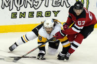New Jersey Devils left wing Jesper Bratt (63) defends against Pittsburgh Penguins defenseman Kris Letang (58) during the first period of an NHL hockey game, Sunday, April 11, 2021, in Newark, N.J. (AP Photo/Kathy Willens)