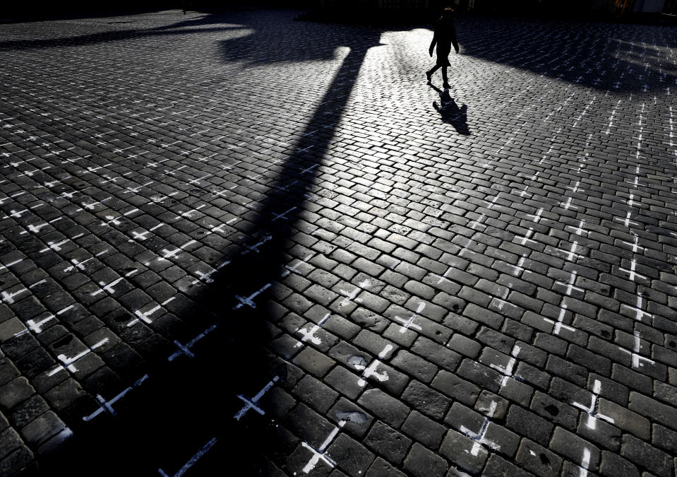 A woman walks through the Old Town Square in Prague, Czech Republic, Monday, March 22, 2021. A group of activists painted the crosses to criticize the government's response to the coronavirus pandemic. (AP Photo/Petr David Josek)
