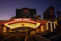 A man walks in front of the Circus Circus hotel and casino in Las Vegas, Feb. 4, 2021. The toll of the coronavirus is reshaping Las Vegas almost a year after the pandemic took hold. The tourist destination known for bright lights, big crowds, indulgent meals and headline shows is a much quieter place these days. (AP Photo/John Locher)