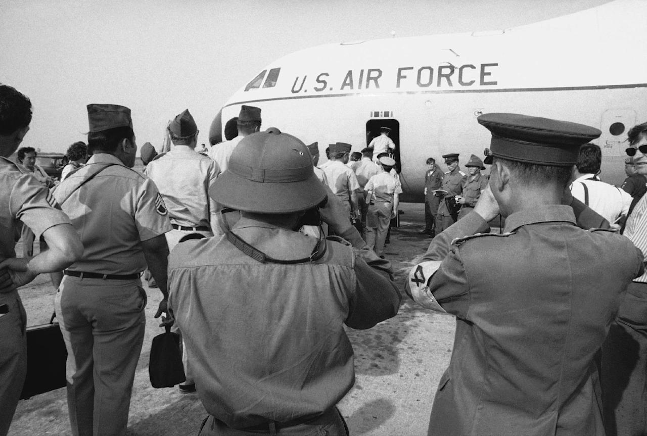 In this March 27, 1973 photo, Viet Cong and North Vietnamese members of the joint military commission, foreground, shoot photos of U.S. troops as they board an Air Force plane for the flight home from Saigon's Tan Son Nhut Air Base. As the last U.S. combat troops left Vietnam 40 years ago, angry protesters still awaited them at home. North Vietnamese soldiers took heart from their foes' departure, and South Vietnamese who had helped the Americans feared for the future. While the fall of Saigon two years later — with its indelible images of frantic helicopter evacuations — is remembered as the final day of the Vietnam War, Friday marks an anniversary that holds greater meaning for many who fought, protested or otherwise lived it. (AP Photo/Neal Ulevich)