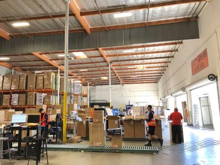 A worker walks passed boxes on a roller conveyor at NewAir's warehouse in Cypress
