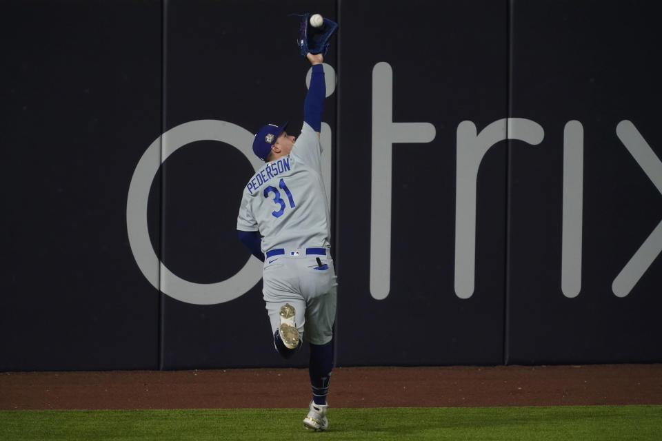 Los Angeles Dodgers left fielder Joc Pederson catches a fly ball hit by Tampa Bay Rays' Joey Wendle during the seventh inning in Game 5 of the baseball World Series Sunday, Oct. 25, 2020, in Arlington, Texas. (AP Photo/Tony Gutierrez)