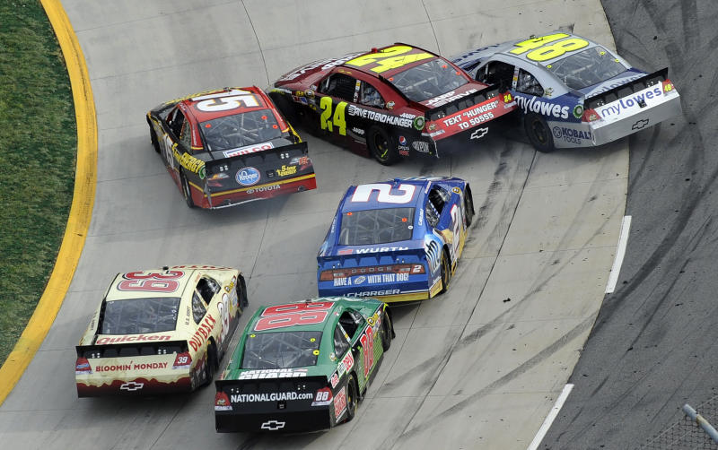 Clint Bowyer (15), Jeff Gordon (24) and Jimmie Johnson (48) get sideways during the closing laps of the NASCAR Sprint Cup Series auto race at Martinsville Speedway in Martinsville, Va., Sunday, April 1, 2012. (AP Photo/LAT, Scott LePage)
