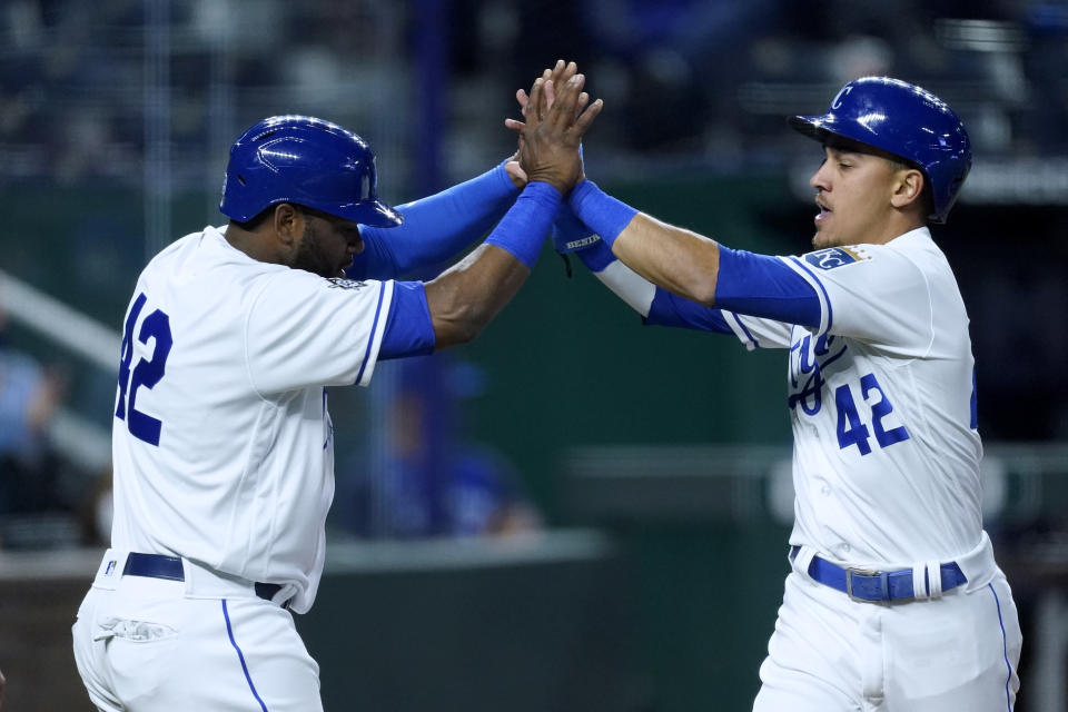 Kansas City Royals' Hanser Alberto, left, and Nicky Lopez celebrate after they scored when Whit Merrifield reached on a fielding error by Toronto Blue Jays' Cavan Biggio during the fourth inning of a baseball game Thursday, April 15, 2021, in Kansas City, Mo. (AP Photo/Charlie Riedel)
