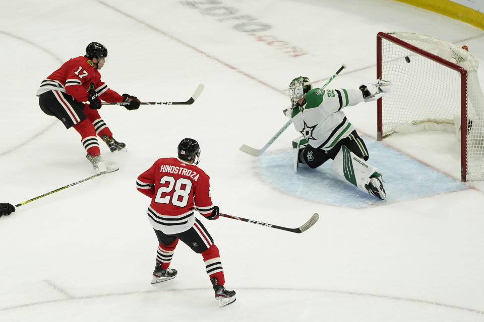 Chicago Blackhawks' Dylan Strome, left, scores past Dallas Stars goaltender Jake Oettinger, right, off an assist from Vinnie Hinostroza, center, during the second period of an NHL hockey game Monday, May 10, 2021, in Chicago. (AP Photo/Charles Rex Arbogast)