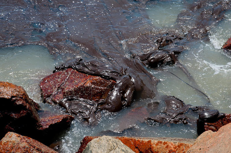 In this Sept. 25, 2019 photo released by the Sergipe state Government, oil sludge pollutes the coast on Sergipe state, Brazil. Oil sludge started landing on Brazil's northeastern coast at the beginning of Sept., authorities say, and have now reached 61 municipalities in nine states, contaminating over 130 beaches. (Sergipe State Government via AP)