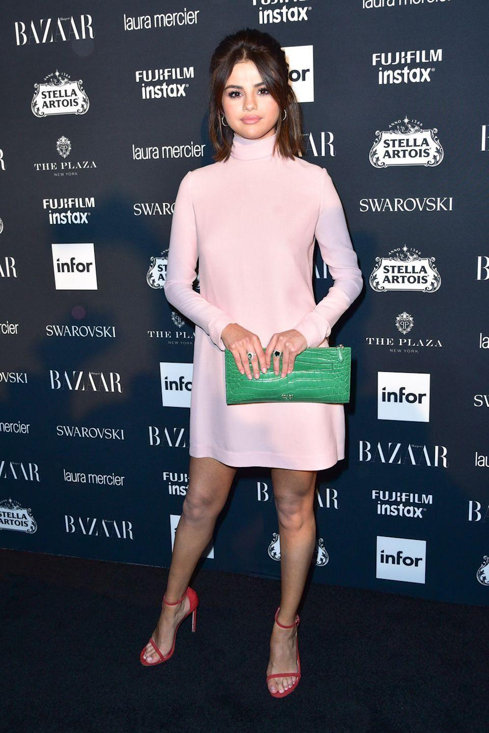 """<p>The star wore a retro-pink dress with a colour-clashing green clutch bag and red heels for the 2017 Harper's Bazaar Icons<span class=""""redactor-invisible-space"""">, September 2017. </span></p>"""