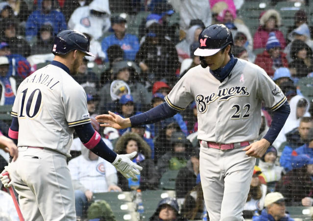 Milwaukee Brewers' Christian Yelich (22) is greeted by Yasmani Grandal (10) after scoring against the Chicago Cubs during the fourth inning of a baseball game, Sunday, May, 12, 2019, in Chicago. (AP Photo/David Banks)