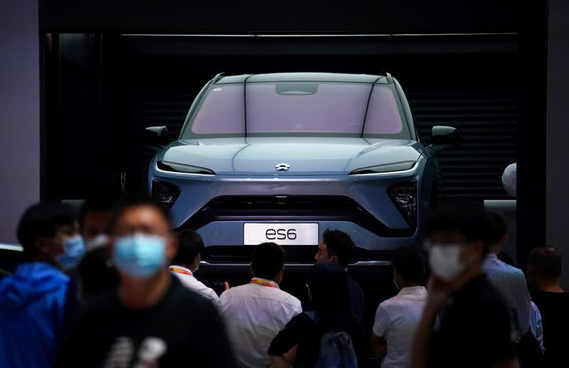 FILE PHOTO: People wearing face masks look at a Nio ES6 EV car at the Beijing International Automotive Exhibition