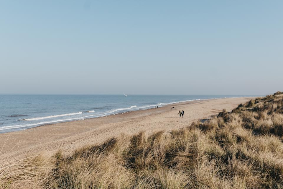 Hemsby, UK - April 19, 2019: Panoramic view from the hill over Hemsby beach on a sunny spring day, two people walking in the distance. Hemsby beach is a famous beach on the East Norfolk coast, UK.