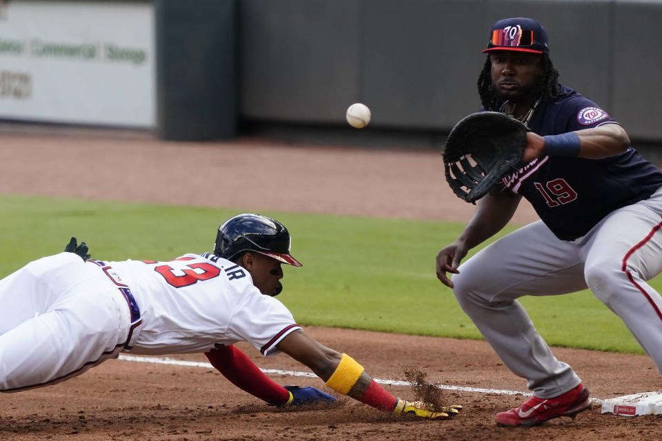 Atlanta Braves' Ronald Acuna Jr. (13) dives back to first base ahead of a throw to Washington Nationals first baseman Josh Bell (19) in the first inning of a baseball game Monday, May 31, 2021, in Atlanta. (AP Photo/John Bazemore)