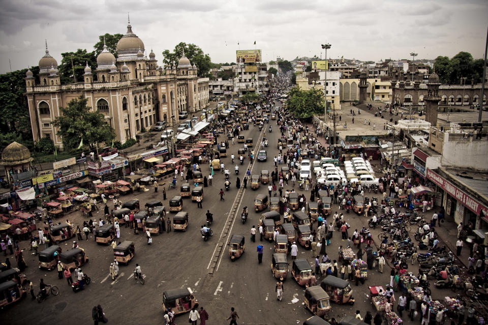 Hustle and bustle of Indian roads around monument of Charminar in Hyderabad, India.Autorickshaws, crowds of people, Ambassador cars, motorbikes, street stalls, and hawkers dominate this colorful photograph of busy Indian intersection.