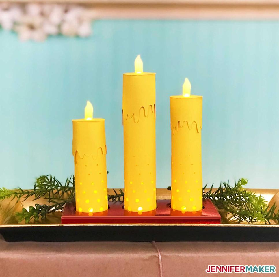 """<p>Make your own paper candles for use in this menorah project. Light them up with LED tealights for a flame-free and worry-free result. Fill the hollow candles with treats like foil-covered chocolates for even more festive fun.</p><p><a href=""""https://jennifermaker.com/3d-paper-candles-menorah-centerpiece"""" target=""""_blank""""><em>Get the tutorial at Jennifer Maker</em></a><br></p>"""
