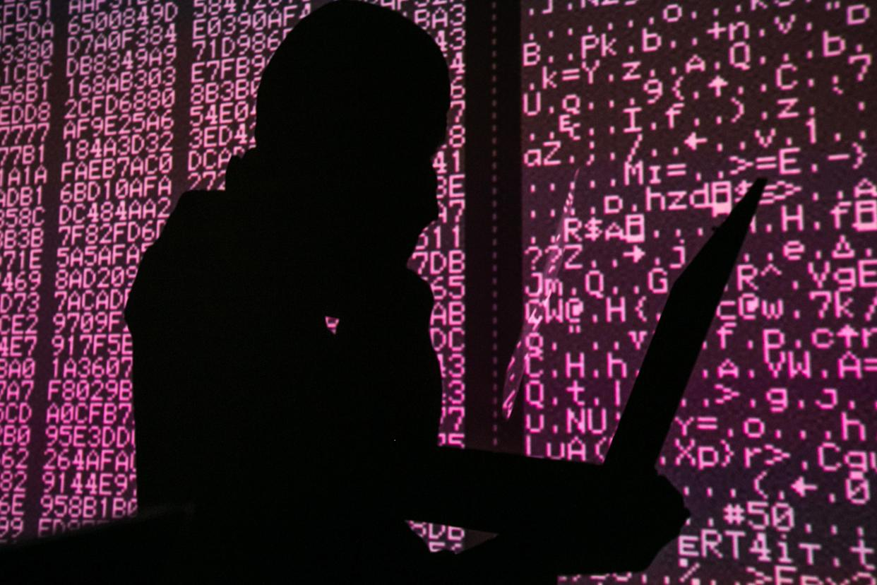 A silhouette of a man in a balaclava mask sitting at a laptop computer, with computer code in the background. (Sergei Konkov\TASS via Getty Images)