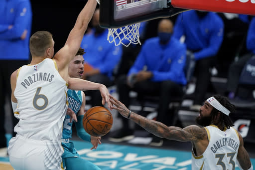 Charlotte Hornets guard LaMelo Ball passes the ball between Dallas Mavericks' Kristaps Porzingis, left, and Willie Cauley-Stein during the first half of an NBA basketball game in Charlotte, N.C., Wednesday, Jan. 13, 2021. (AP Photo/Chris Carlson)