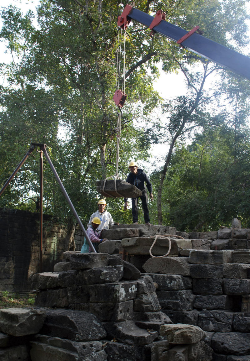 In this photo taken Dec. 12, 2011, using a crane, workers move heavy sandstone blocs from a tower within the Buddhist temple of Banteay Chhmar, Cambodia. It's still entwined in mystery and jungle vines, but one of Cambodia's grandest monuments is slowly awakening after eight centuries of isolated slumber, having attracted a crack archaeological team and a trickle of tourists.    (AP Photo/Denis Gray)