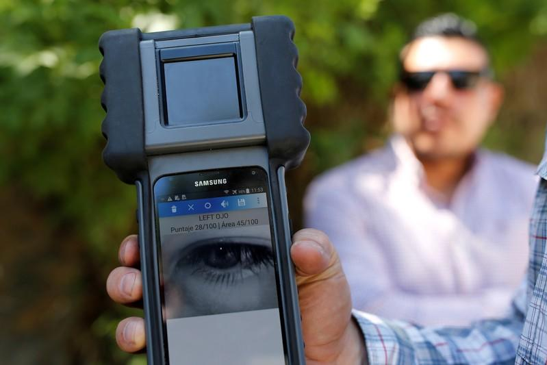 FILE PHOTO: An agent of the U.S. Department of Homeland Security shows a retinal scanner, tested on a fellow agent, at a checkpoint of the Guatemala's border police (DIPAFRONT) in El Progreso