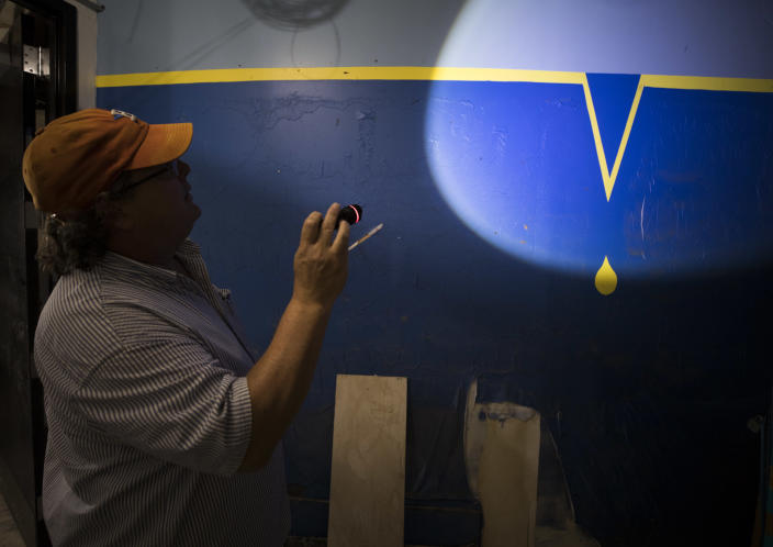 Alley Theatre general manager Ten Eyck Swackhamer shines his flashlight on the high-water mark from Tropical Storm Allison painted on a wall in the lower section of the theater that was flooded by Hurricane Harvey in Houston on Sept. 8, 2017. The high-water mark from Hurricane Harvey was about two feet above that. (Photo: Erich Schlegel for Yahoo News)