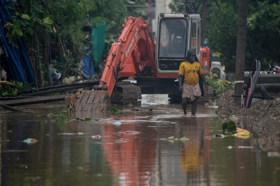 A resident wades through a waterlogged road after heavy rains following Cyclone Nivar landfall in Puducherry on November 26, 2020. (Photo by ARUN SANKAR/AFP via Getty Images)