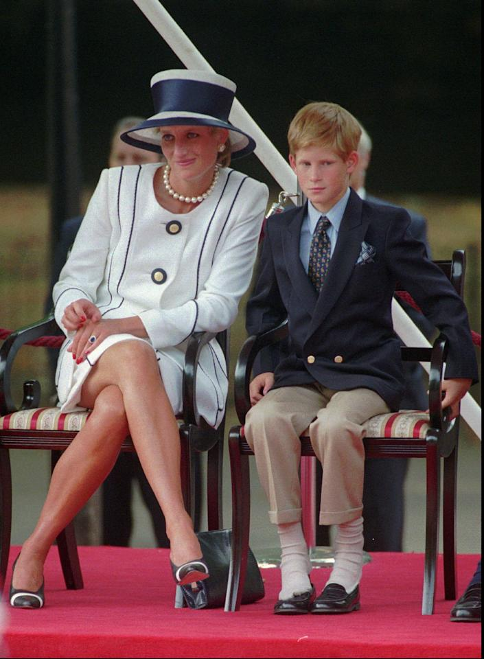 Britain's Princess of Wales sits next to her yougest son Prince Harry during V-J day celebrations in London Saturday August 19, 1995. Prince Harry sits with his feeting resting on his shoes. (AP Photo/Alastair Grant)