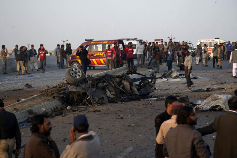 People gather at the site of bombing in Karachi, Pakistan, Thursday, Jan. 9, 2014. Police said a car bomb has killed a senior police investigator known for arresting dozens of Pakistani Taliban, as well as two other officers. (AP Photo/Shakil Adil)