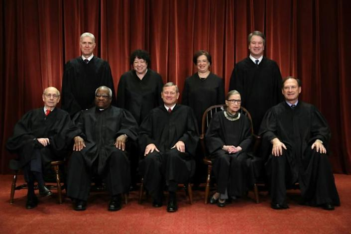 Chief Justice John Roberts (C, sitting) with the other members of the US Supreme Court (AFP Photo/CHIP SOMODEVILLA)