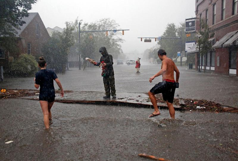 People survey the damage caused by Hurricane Florence on Front Street in downtown New Bern, North Carolina on Friday.