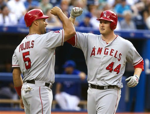 Los Angeles Angels' Mark Trumbo, right, is congratulated at home plate by Albert Pujols after hitting a two-run home run off Toronto Blue Jays starting pitcher Brett Cecil in the fourth inning of a baseball game in Toronto, Thursday, June 28, 2012. (AP Photo/The Canadian Press, Fred Thornhill)