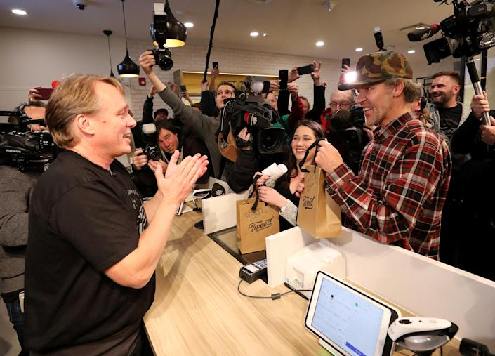 <p>Canopy Growth CEO Bruce Linton applauds after handing Ian Power and Nikki Rose, who were first in line to purchase the first legal recreational marijuana after midnight, their purchases at a Tweed retail store in St John's, Newfoundland and Labrador, Canada, Oct. 17, 2018. (Photo: Chris Wattie/Reuters) </p>