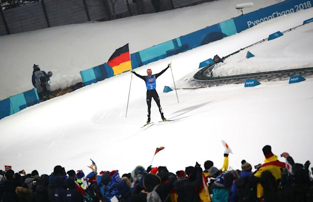Nordic Combined Events - Pyeongchang 2018 Winter Olympics - Men's Team 4 x 5 km Final - Alpensia Cross-Country Skiing Centre - Pyeongchang, South Korea - February 22, 2018 - Johannes Rydzek of Germany waves the German flag as he approaches the finish line. REUTERS/Carlos Barria