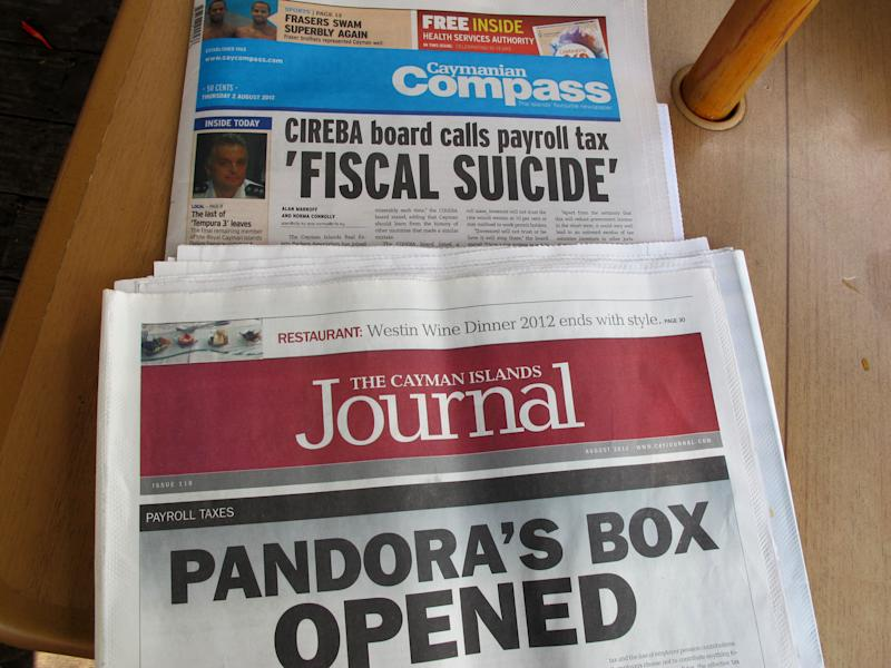 In this Aug. 2, 2012 photo, local newspapers show stories about the controversial strategy to bail the government out of a financial hole, at a restaurant along Seven Mile Beach on the outskirts of George Town on the Cayman Islands. The Cayman Islands have lost some of their allure by abruptly proposing what amounts to an income tax on expatriate workers who have helped build the territory into one of the most famous or, for some people, notorious offshore banking centers that have tax advantages for foreign investment operations. (AP Photo/David McFadden)