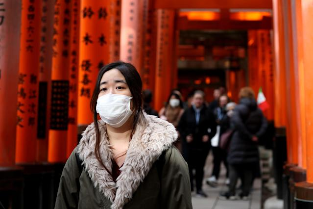 A woman is pictured wearing a mask in the near-empty Torii gates at Fushimi Inari-taisha shrine in Kyoto on 6 March. The tourist attraction is usually overrun with visitors. Japan has 381 confirmed cases. (Getty Images)