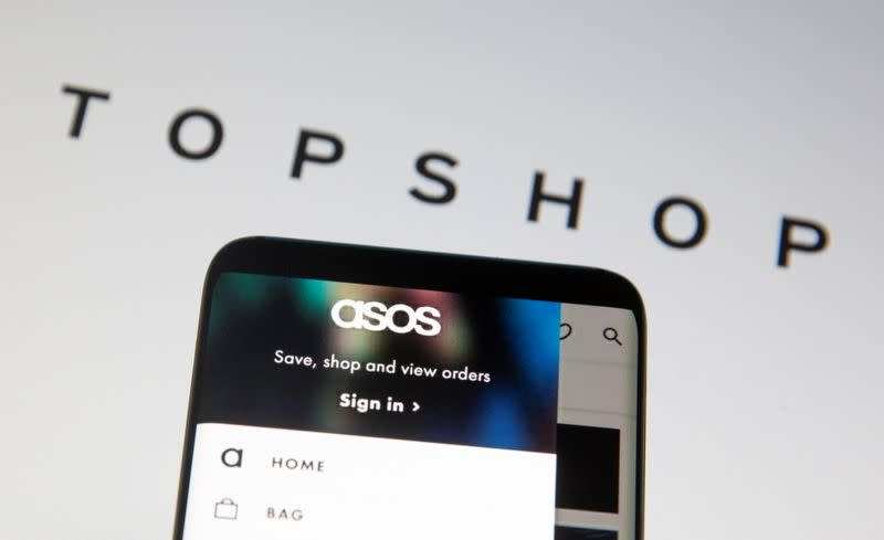 Asos logo is seen in a smartphone in front of a displayed TopShop logo in this illustration