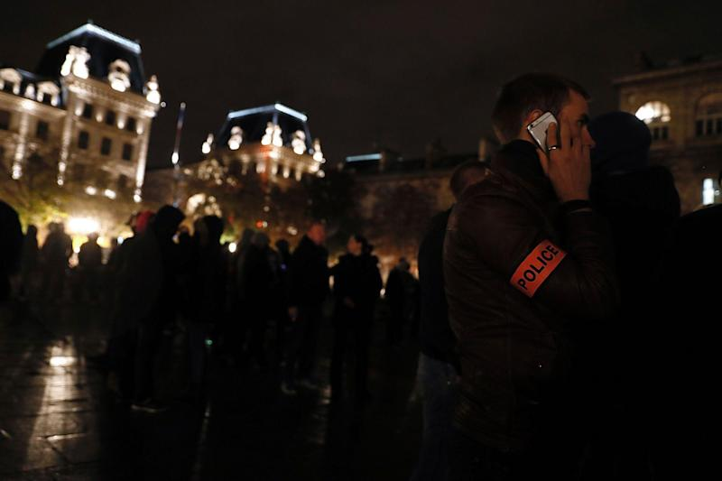 A French police officer talks on his mobile phone outside the Notre-Dame Cathedral in Paris: THOMAS SAMSON/AFP/Getty Images