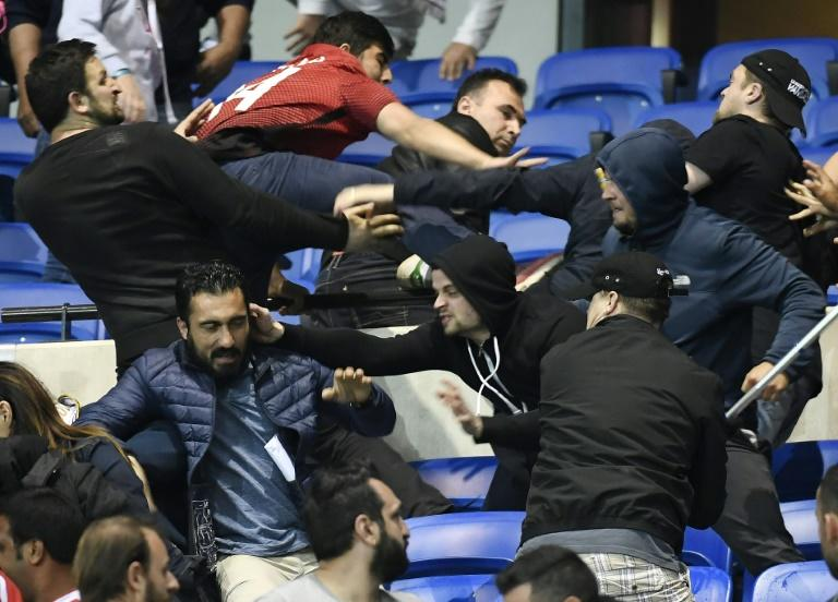 Besiktas' and Lyon's supporters fight before their UEFA Europa League first leg quarter final football match on April 13, 2017, at the Parc Olympique Lyonnais stadium in Decines-Charpieu, central-eastern France