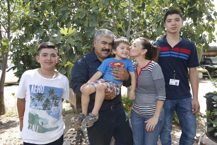 """From left, Roman, Ruben, Rafael, Katy, and Ruben, pose for an photo in front of their house in Tucson, Ariz., on Tuesday, Sept. 4, 2018. Moroyoqui, 45, entered the country with authorization 16 years ago but then overstayed his visa, not wanting to return home because of the lack of opportunity there. He has four U.S. citizen children and said he has been a faithful taxpayer. """"I feel great respect and love for this country,"""" he said. (AP Photo/Rick Scuteri)"""