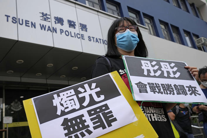 """Chow Hang Tung, Vice Chairperson of the Hong Kong Alliance in Support of the Democratic Patriotic Movements of China, holds placards after being released on bail at a police station in Hong Kong, Saturday, June 5, 2021. Hong Kong police on Friday, June 4, arrested Chow for publicizing an unauthorized assembly via social media despite the police ban on the annual June 4 candlelight vigil. The placards read: """"Innocent of candlelight, Tung Tung will return from victory."""" (AP Photo/Kin Cheung)"""