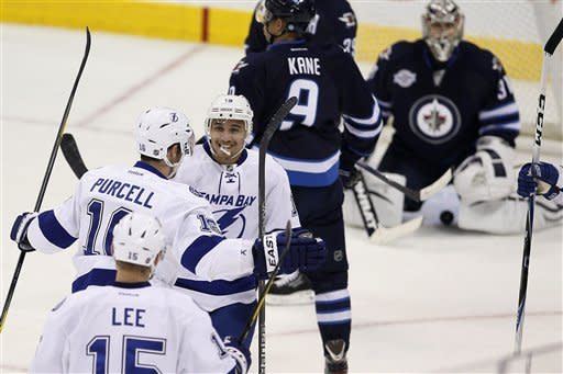 Tampa Bay Lightning's J.T. Brown (19) and Teddy Purcell (16) celebrate Purcell's goal against the Winnipeg Jets during the first period of an NHL hockey game in Winnipeg, Manitoba, Saturday, April 7, 2012. (AP Photo/The Canadian Press, John Woods)