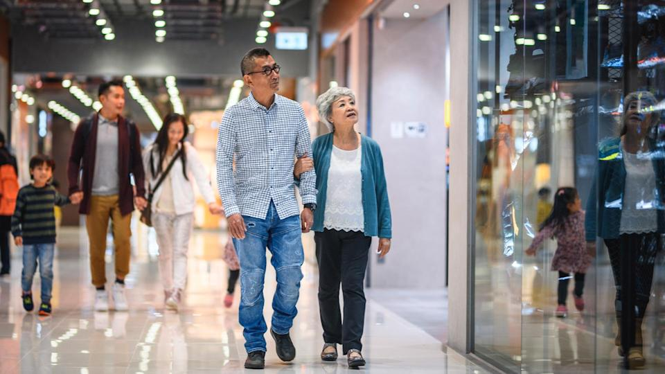 Senior Chinese man and woman walking arm in arm through Harbour City Shopping Centre with younger family members in background.