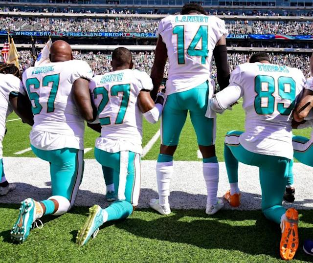 Miami Dolphins players kneel in protest during the national anthem before the start of an NFL game against the New York Jets at MetLife Stadium