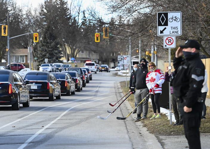 People honor and pay their respects as the funeral procession for Walter Gretzky passes by in Brantford, Ontario, on Saturday, March 6, 2021. Walter Gretzky also know as Canada's hockey dad was 82 years old. (Nathan Denette/The Canadian Press via AP)