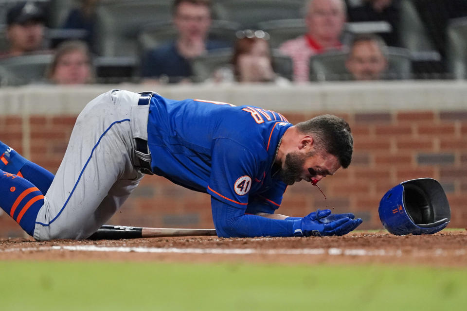 New York Mets' Kevin Pillar (11) tries to get to his feet after being hit in the face with a pitch from Atlanta Braves pitcher Jacob Webb in the seventh inning of a baseball game Monday, May 17, 2021, in Atlanta. (AP Photo/John Bazemore)