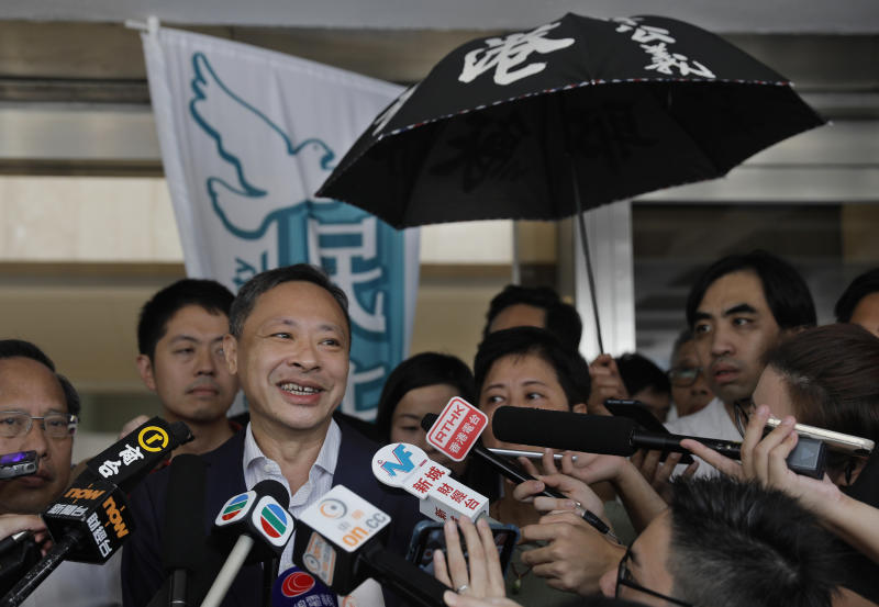Occupy Central leader Benny Tai, center, talks to reporters outside the High Court in Hong Kong Thursday, Aug. 15, 2019. Tai, a top opposition leader imprisoned on public disorder charges was released on bail Thursday as Hong Kong's government attempts to quell a protest movement that has paralyzed parts of the territory, including its international airport, and led to hundreds of arrests. (AP Photo/Vincent Yu)
